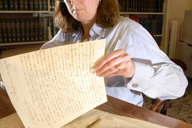 Whether you're tracing your family tree, writing a historical novel or taking on a personal research project to uncover an unfamiliar historical idea or period, you will need to conduct some research to further your knowledge and understanding. Here, history professor Martha McNamara studies documents she found at the Maine Historical Society library while researching a book. (Photo by John Ewing/Portland Press Herald via Getty Images)