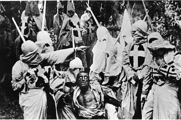 A picture from DW Griffith's 1915 film 'The Birth of a Nation'. Actors costumed in the full regalia of the Ku Klux Klan chase down a white actor in 'blackface'. (Photo by Hulton Archive/Getty Images)