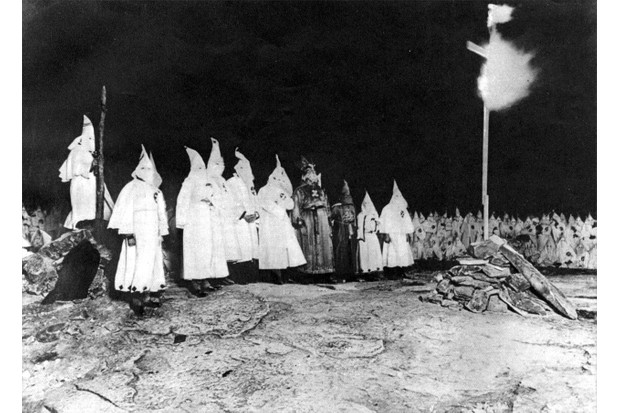 Members of the Ku Klux Klan burn a cross, Baltimore, Maryland, 1923. It was claimed that the Klan robes, hoods, and masks made it impossible to identify Klan members, though Linda Gordon explains that in most communities the identities of Klansmen were well known. (Photo by Transcendental Graphics/Getty Images)