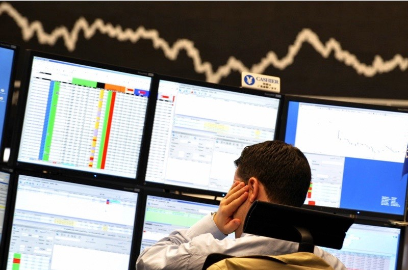 A broker looks at his screens at Frankfurt's stock exchange on 15 September 2008. (Photo by Thomas Lohnes/AFP/Getty Images)