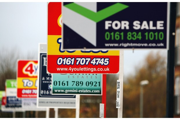 A row of 'For sale' and 'To let' signs stand outside a housing development in Salford, Greater Manchester, 26 November 2008. (Photo by Christopher Furlong/Getty Images)