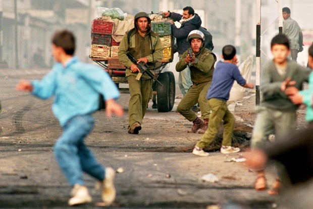 Young Palestinians flee Israeli soldiers during riots in Gaza City in 1993