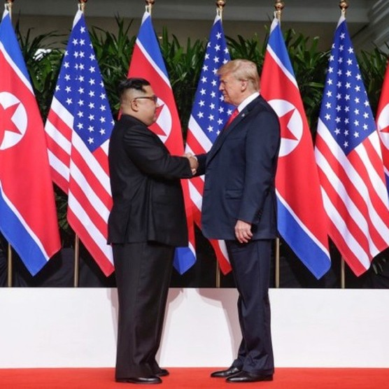 US president Donald Trump and the North Korean leader Kim Jong-un shake hands at a summit in Singapore on 12 June 2018. (Photo by Handout/Getty Images)