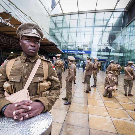 Actors dressed as Tommies mark the centenary of the start of the battle of the Somme at Manchester Piccadilly station, July 2016. (Photo by Alamy)
