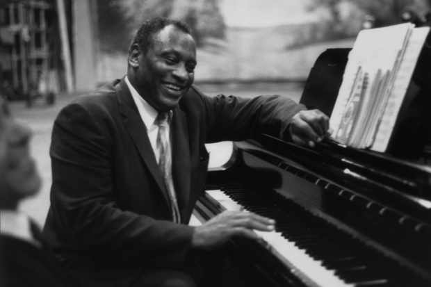 "Singer Paul Robeson rehearses at a piano in 1958. He had a unifying outlook, observing that ""neither suffering nor compassion is confined to one face."" (Photo by Keystone Features/Getty Images)"