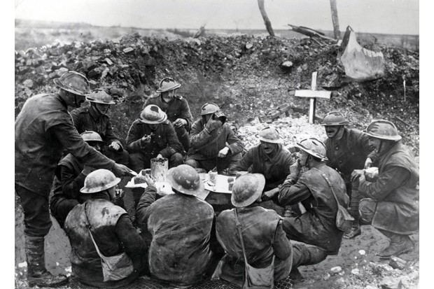 Soldiers on the western front in France in a happy mood as they eat a meal to celebrate Christmas Day in a shell hole partly occupied by the grave of a comrade (Paul Popper/Popperfoto/Getty Images)