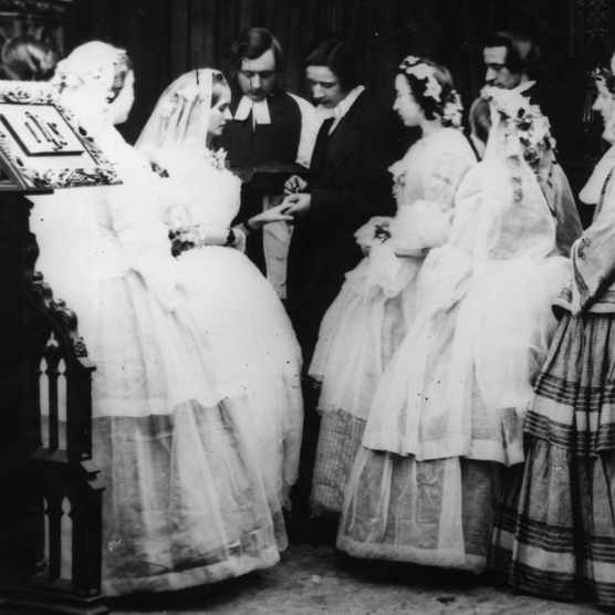 """""""With this ring..."""" A young couple say their vows in c1860, watched by bridesmaids and a clergyman – but much about Victorian weddings wasn't quite so familiar. (Photo by London Stereoscopic Company/Getty Images)"""