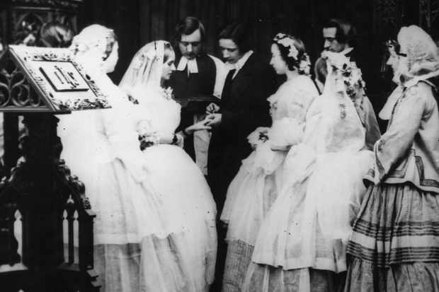 """With this ring..."" A young couple say their vows in c1860, watched by bridesmaids and a clergyman – but much about Victorian weddings wasn't quite so familiar. (Photo by London Stereoscopic Company/Getty Images)"