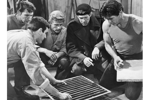 An unidentified actor removes a metal grate from the floor as actors (left–right) Lawrence Montaigne, John Leyton, James Coburn and Charles Bronson look on. From the film, 'The Great Escape,' directed by John Sturges, 1963. (Photo by United Artists/Courtesy of Getty Images)