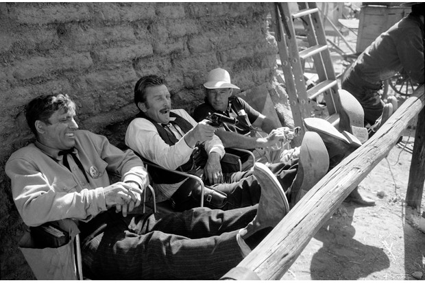 Actor Kirk Douglas (centre) aims a gun while actor Burt Lancaster (left) and American director John Sturges watch during a break in filming 'Gunfight at the O.K. Corral,' directed by Sturges, 1957. (Photo by Ralph Crane/The LIFE Picture Collection/Getty Images)