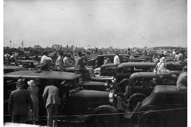 Spectators clamber onto the roofs of their cars to watch the 1935 Royal Air Force Pageant at Hendon Aerodrome, London. (Photo by J. A. Hampton/Topical Press Agency/Getty Images)