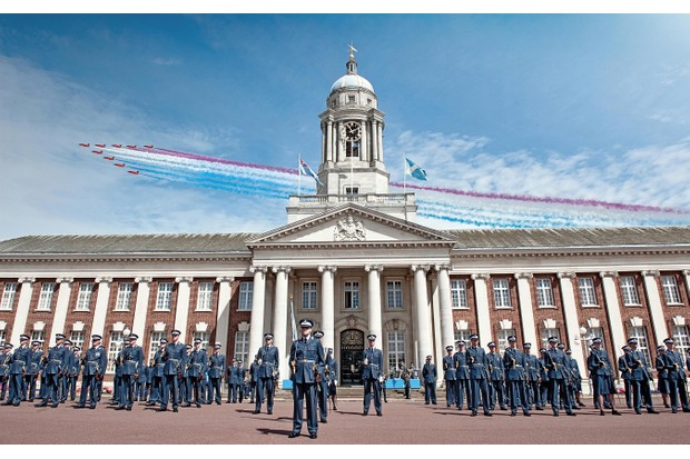 Officer cadets stand on parade at the RAF College at Cranwell in Lincolnshire, whilst the Red Arrows display team performs a flypast. (UK MOD © Crown copyright 2018)
