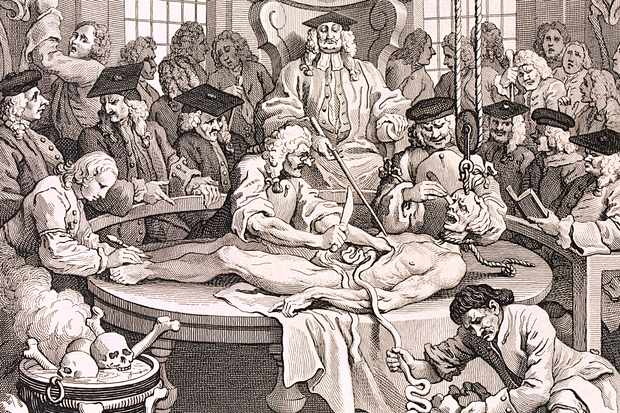 This engraving by William Hogarth shows the final instalment of a sequence of artworks called 'The Four Stages of Cruelty' (1751). In it, the fictional Tom Nero is being dissected for anatomical studies at Cutlerian theatre near Newgate prison after being hanged for murder. Nero looks like the Dead-Alive, as though he can see and smell his own executed body on the dissection table. The chief physician sits in the centre on a high-backed chair, resembling a high court judge. He is surrounded by various medical men, including penal surgeons, who did gallows work. The skeletons of dissected criminals were usually refused a Christian burial and so were displayed as specimens, as can be seen top left and top right. (Photo by Guildhall Library/Getty Images)