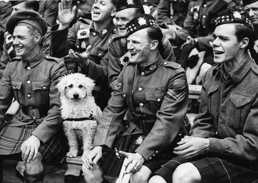 c1943: Soldiers enjoy a baseball match at Wembley Stadium in London between the United States Army and Canadian Forces. With them sits Bobby, the mascot of the Canadian Highland Scottish regiment. (Photo by Hulton-Deutsch Collection/CORBIS/Corbis via Getty Images)