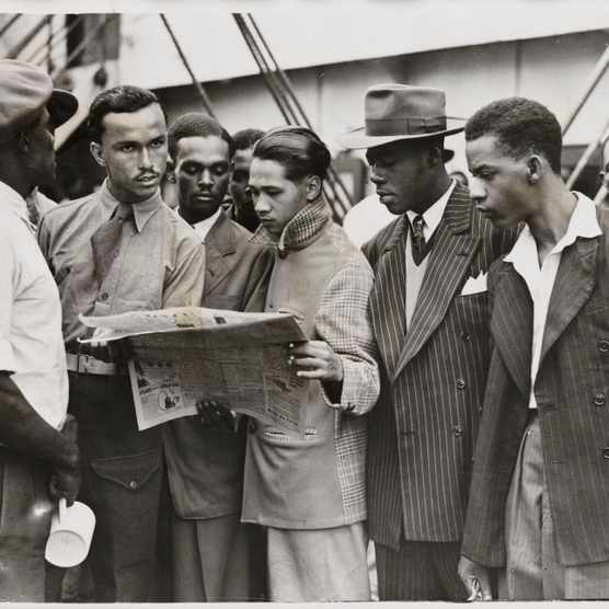 """Passengers reading a newspaper while waiting to disembark from the 'Empire Windrush' at Tilbury, having sailed from Jamaica, taken by an unknown photographer for the Daily Herald newspaper, 21 June 1948. """"The Windrush scandal would have been inconceivable if we knew that those we are deporting not only helped to build the welfare state but were either born as, or to subjects of, the British state"""", says Professor Kehinde Andrews. (Photo by Daily Herald Archive/SSPL/Getty Images)"""