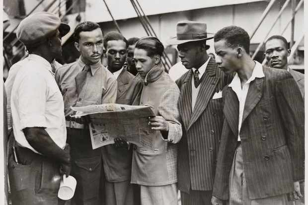 "Passengers reading a newspaper while waiting to disembark from the 'Empire Windrush' at Tilbury, having sailed from Jamaica, taken by an unknown photographer for the Daily Herald newspaper, 21 June 1948. ""The Windrush scandal would have been inconceivable if we knew that those we are deporting not only helped to build the welfare state but were either born as, or to subjects of, the British state"", says Professor Kehinde Andrews. (Photo by Daily Herald Archive/SSPL/Getty Images)"