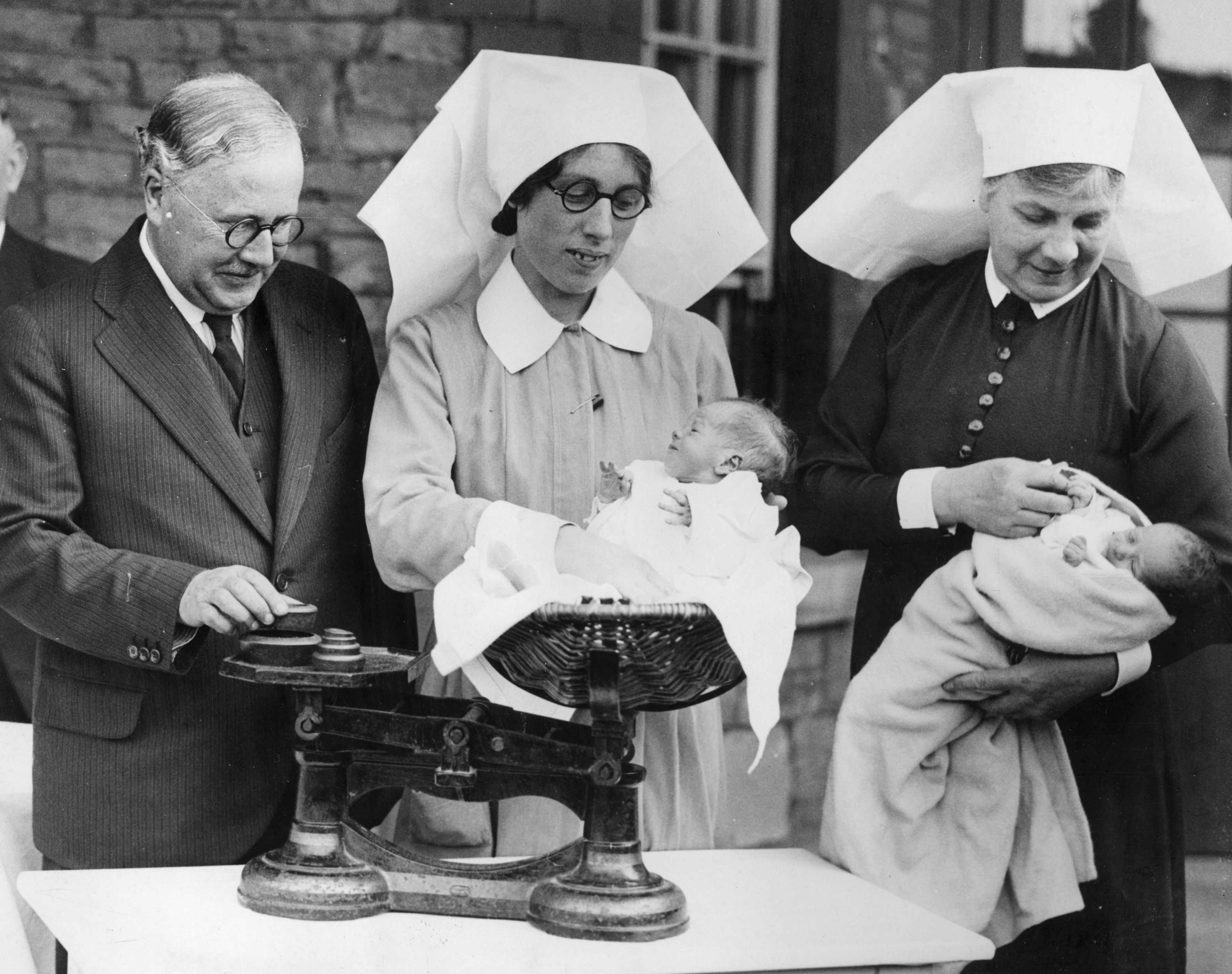 17th September 1936: The British minister of health, Sir Kingsley Wood, watches nurses weighing newborn twins during a visit to Southmead Hospital in Bristol to see the work local authorities were doing for the maintenance and improvement of health and housing conditions. (Photo by Fox Photos/Getty Images)