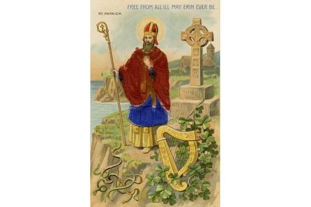 A St Patrick's Day postcard depicts St Patrick standing on cliff side, with blue robes, chasing the snakes from Ireland. (Image by Jim Heimann Collection/Getty Images)