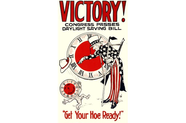 A US Government poster from 1918 showing Uncle Sam turning adjusting a clock for summertime. (Photo by VCG Wilson/Corbis via Getty Images)