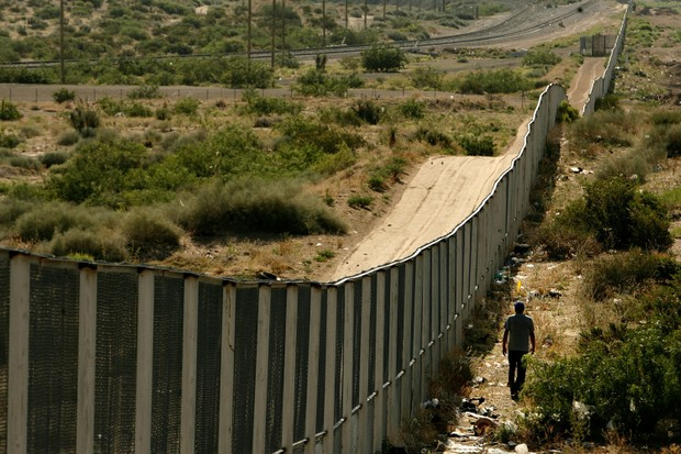A man walks along the border fence between the US and Mexico in the Anapra area of Ciudad Juárez, Mexico. (Photo by Chip Somodevilla/Getty Images)