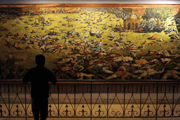 A young visitor looks at a painting depicting the Amritsar Massacre
