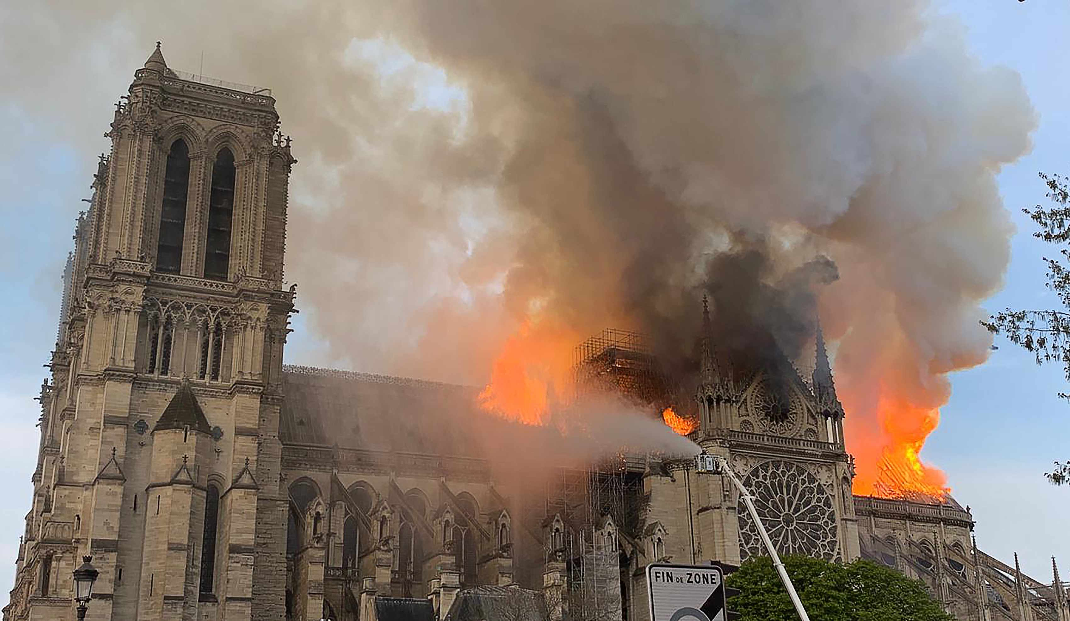 "Flames and smoke are seen billowing from the roof at Notre-Dame cathedral in Paris, 15 April 2019. Yet despite the devastation, the fire is ""not the worst chapter in its 850-year history"", argues Dr Emily Guerry. (Patrick Anidjar/AFP/Getty Images)"