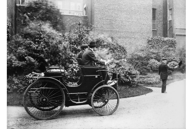 Motorcar manufacturer Charles Stewart Rolls in his first motor car in the late 19th-century, with a man walking in front with a red flag as the law of the time required. (Photo by Topical Press Agency/Getty Images)