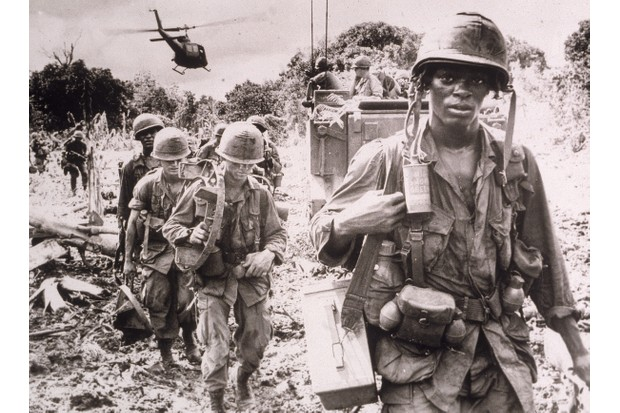 After receiving a fresh supply of ammunition and water flown in by helicopter, men of the US 173rd Airborne Brigade continue on a jungle 'search and destroy' patrol in Phước Tuy Province, Vietnam, June 1966. An armoured personnel carrier provides security on the landing zone in the background. (Photo by Hulton Archive/Getty Images)