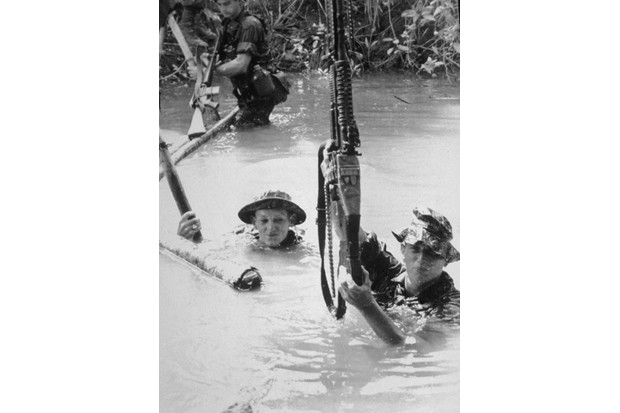 American army combat platoon leader First Lieutenant Alex C Green (right) and two unidentified soldiers carry weapons as they wade through a deep stream during operations in Vietnam, late 1960s. (Photo by Hulton Archive/Getty Images)