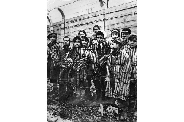 A group of children behind a barbed wire fence at the Nazi concentration camp at Auschwitz-Birkenau. Although anti-Semitism has a long history, it reached genocidal heights in Nazi Germany. (Photo by Alexander Vorontsov/Keystone/Hulton Archive/Getty Images)