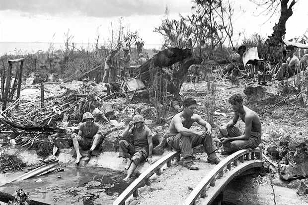 Troubled waters: American soldiers rest on a decorative bridge during the crucial, bloody battle for Saipan in the Pacific Ocean. Victory put Japan in range of the US heavy bombers. (Photo by Peter Stackpole/The LIFE Picture Collection/Getty Images)