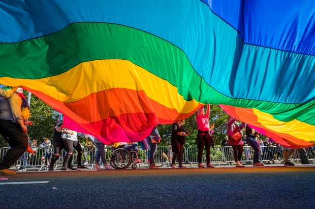 People march with a large rainbow flag in Reykjavik, Iceland. (Image by Photolibrary / Getty Images Plus)