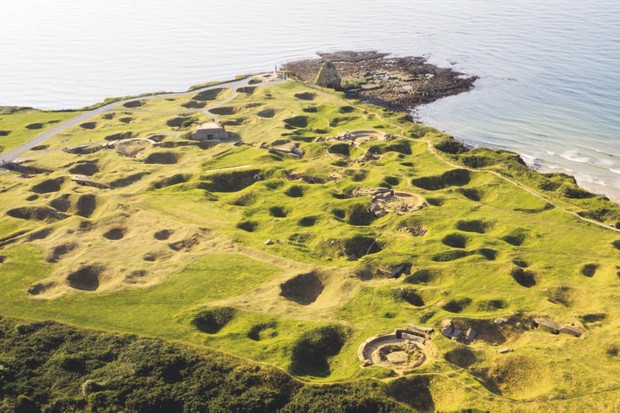 Looking out across the Channel, shell craters pockmark Pointe du Hoc – a German artillery position seized by US Rangers. The promontory is one of many reminders of D-Day along the Normandy coastline. (Photo by Getty Images)