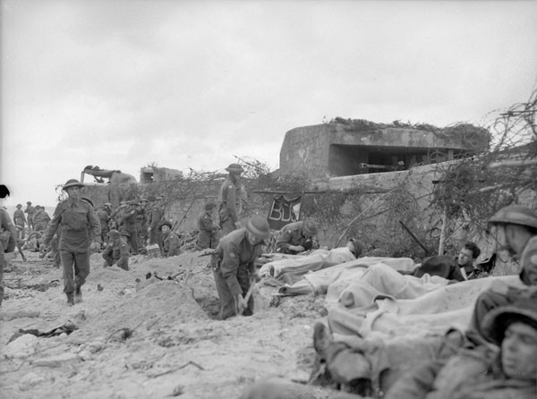 Wounded Canadian soldiers awaiting transfer to a casualty clearing station of the Royal Canadian Army Medical Corps, Courseulles-sur-Mer. (Credit: Lieut. Frank L. Dubervill / Canada. Dept. of National Defence / Library and Archives Canada / PA-132384)