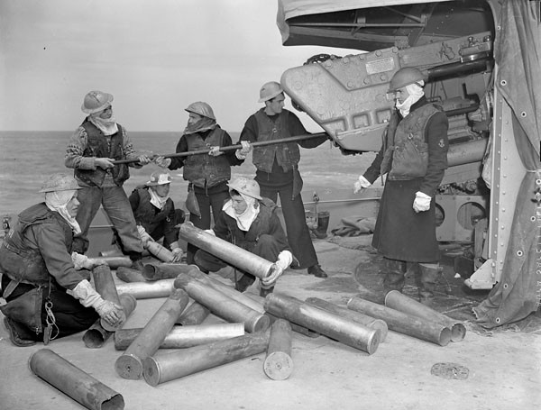 A gun crew of the destroyer HMCS Algonquin piling shell cases and sponging out the gun after bombarding German shore defences in the Normandy beachhead. (Credit: Lt Richard G. Arless / Canada. Dept. of National Defence / Library and Archives Canada / PA-157805)