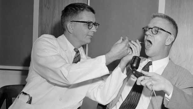 CIA researcher Carl Pfeiffer (right) is given a dose of LSD; he would later administer it to prisoners. (Image by Bettmann/Getty Images)