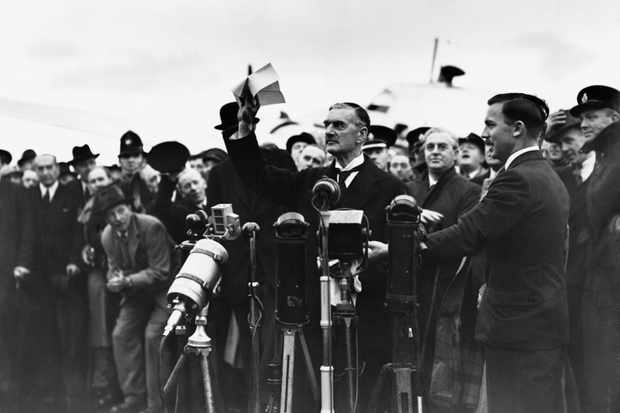 "Prime Minister Neville Chamberlain waves to the crowd at Heston Airport and declaims ""Peace in our Time"" after returning from signing the Munich Agreement. (Photo by © Hulton-Deutsch Collection/CORBIS/Corbis via Getty Images)"