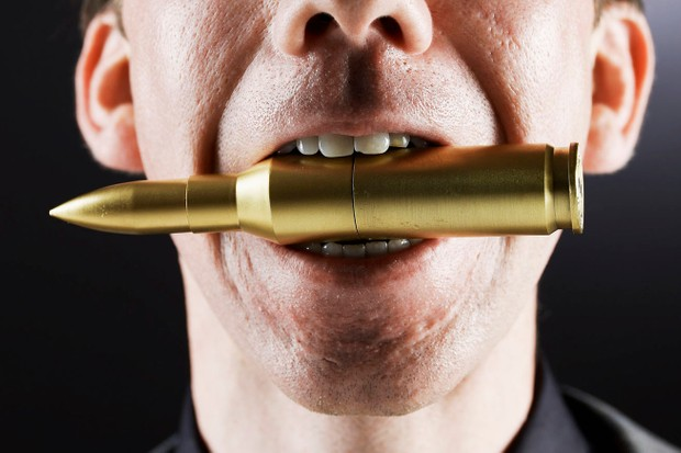 Man biting a bullet