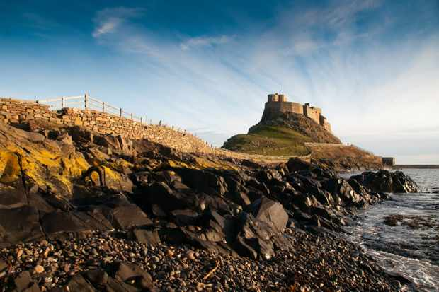 High heaven: Lindisfarne Castle rises above the beach. It's a steep climb to the castle entrance. (Photo by Alamy)