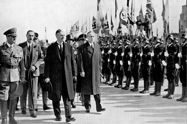 British Prime Minister Neville Chamberlain passes a Nazi honour guard on his arrival in Germany in 1938, accompanied by Joachim von Ribbentrop (right). (Photo by Ann Ronan Pictures/Print Collector/Getty Images)