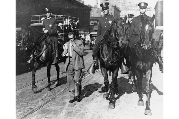 Mounted police flanking a black man during Chicago's 1919 race riot