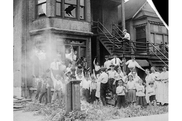 A group of children celebrate after setting a black family's home on fire.