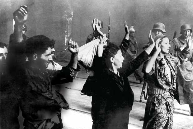 Jews stand with hands up before German soldiers