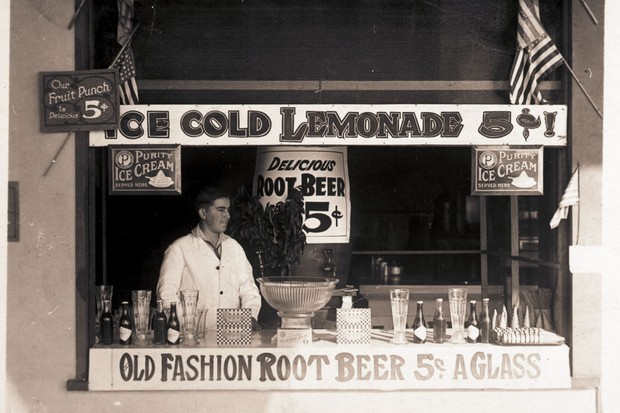 A vintage photograph showing an unknown man standing behind a stall selling lemonade, root beer and ice cream –among other things.