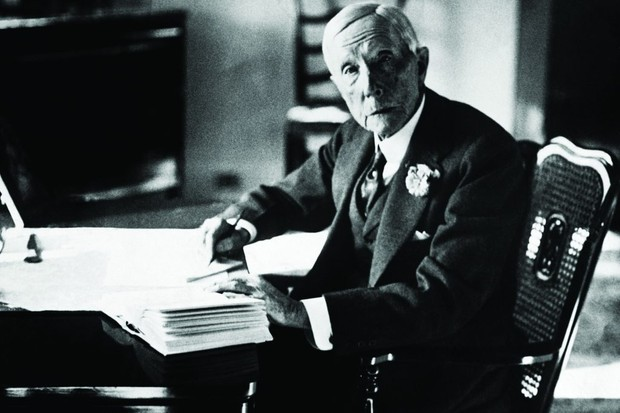 American business magnate JD Rockefeller sits at a desk