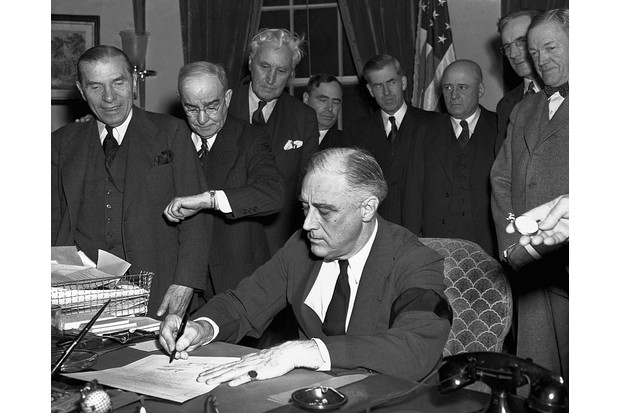 President Roosevelt, wearing a black armband, signs the United States' declaration of war against Japan.