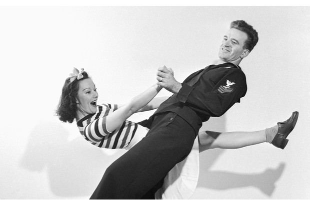 A sailor and woman dance the jitterbug