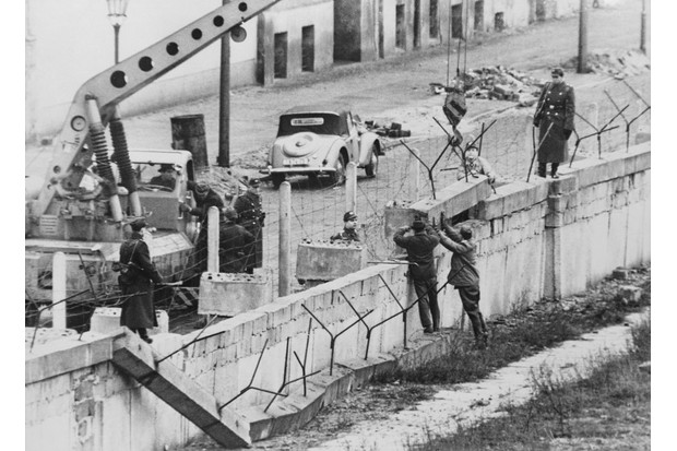 January 1962: Members of the East German Volkspolizei (police) repair a damaged section of the Berlin Wall. (Photo by Keystone/Hulton Archive/Getty Images)