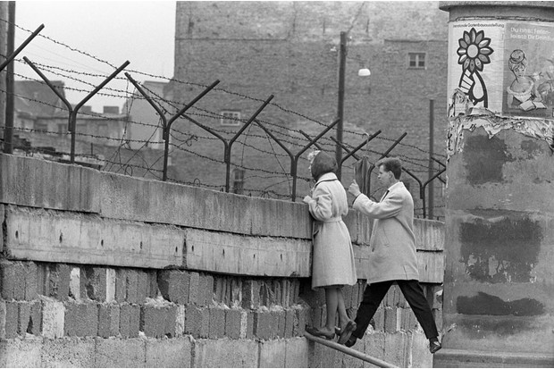 A young man and woman stand near the top of the Berlin Wall to talk to someone on the opposite side. (Photo by Getty Images)