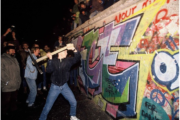 9 November 1989: A young man in East Berlin attacks the Berlin Wall following news that the government would grant exit visas to anyone wishing to go to the west. Within hours, people were smashing sections of the wall – leading to the complete opening of the border within days. (Photo by robert wallis/Corbis via Getty Images)